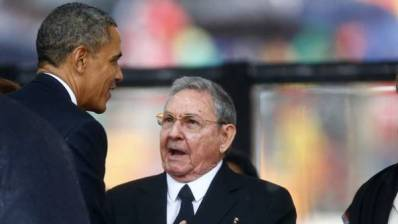 Los presidentes Raúl Castro y Barack Obama durante un breve intercambio en Suráfrica en diciembre de 2013.