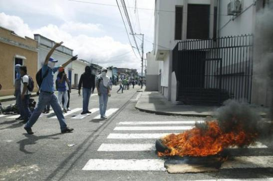 Masked students block a street during a protest against the government in San Cristobal
